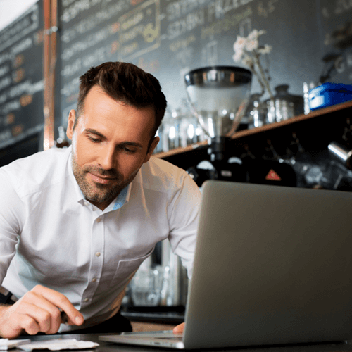 man using laptop - coffee shop - food and beverages supplies
